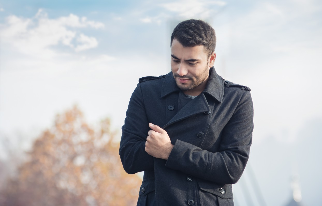 Man in coat feel cold and looking down with crossed their arms on winter or autumn day. Outdoors, outside