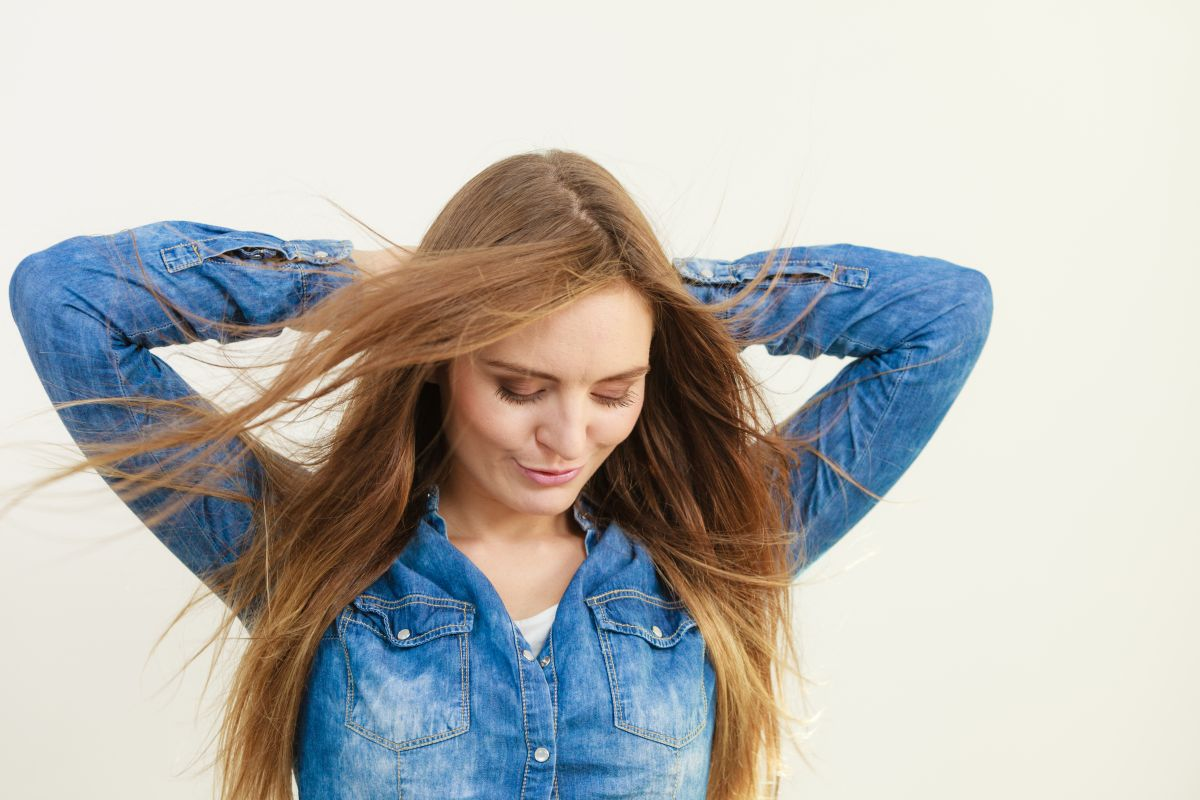 Female fashion and haircare. Fashionable young attractive woman wearing denim jeans shirt. Girl with brown long hair waving on air. Lady take care of hairdo.